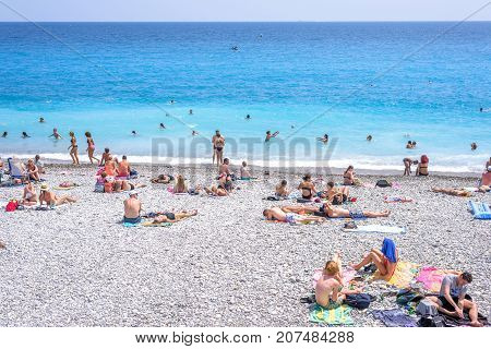 NICE COTE D'AZUR, FRANCE - JUNE 27,2017: Beautiful daylight view to famous beach. Blue water with people walking on sand.