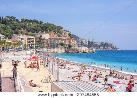 NICE COTE D'AZUR, FRANCE - JUNE 27,2017: Beautiful daylight view to famous beach. Blue water with people walking on sand. Buildings on background.