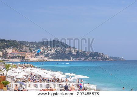 NICE COTE D'AZUR, FRANCE - JUNE 27,2017: Beautiful daylight view to beach resort. Blue water with people walking on sand.