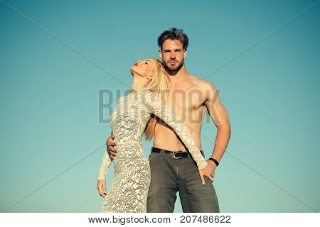 Relationship heterosexual relationship and lifestyle concept. Couple in love on blue sky. Woman or girl with long blond hair in lace dress. Man or macho with torso in jeans. Fashion and beauty.