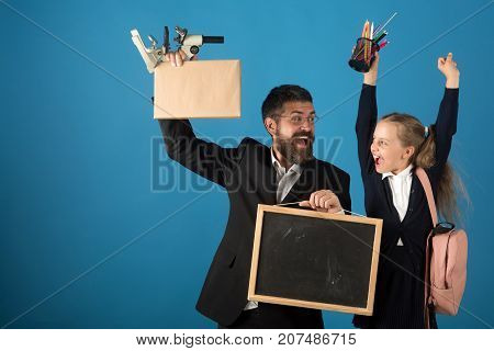 Kid and dad hold microscope blackboard book and stationery. Father and schoolgirl with cheerful faces on blue background copy space. Home schooling and back to school concept. Girl and bearded man