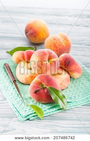 Ripe peaches on a green cloth napkin on a wooden background
