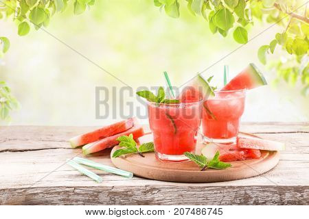 Two glasses with a refreshing cold cocktail of watermelon with mint and lime on a wooden tray on a background of green leaves