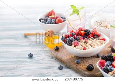 Healthy food for breakfast. Oatmeal with fresh berries and honey. Wooden light table. copy space