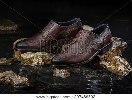 Stylish leather men shoes on a black background
