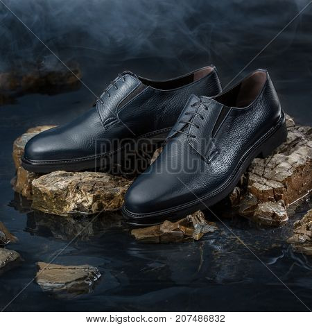 Fashionable leather shoes on a stone in water. Studio photo
