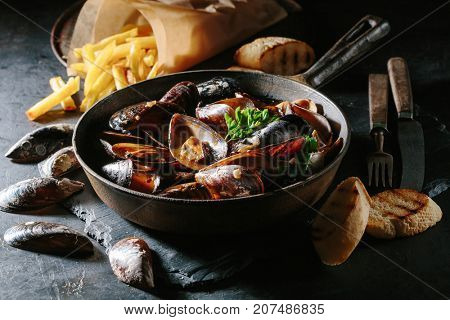 Freshly prepared mussels in tomato sauce with toasts and French fries on a dark stone background