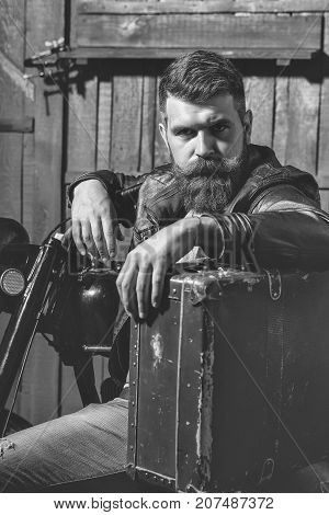 Bearded man hipster biker brutal male with beard and moustache in leather jacket sits near motorcycle with vintage suitcase on wooden background