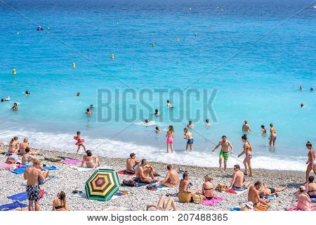 NICE COTE D'AZUR, FRANCE - JUNE 27, 2017: Beautiful daylight view. Blue water with people walking on sand.