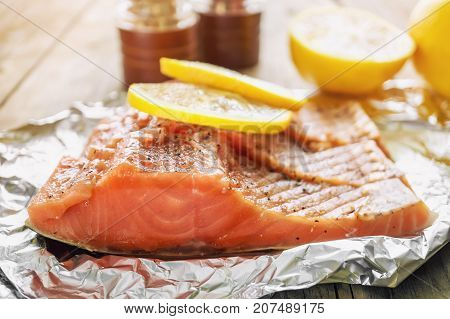 Big pink piece of salmon with herbs and lemon rests on a shiny piece of foil. The horizontal frame.