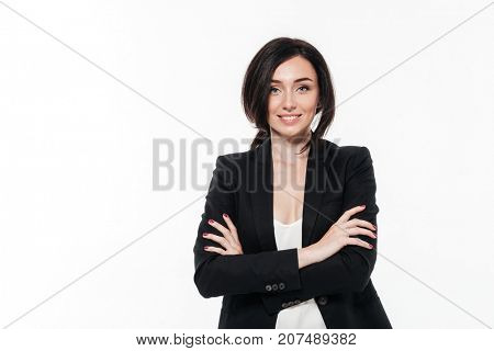 Portrait of a beautiful smiling businesswoman in a suit posing while standing with arms folded isolated over white background