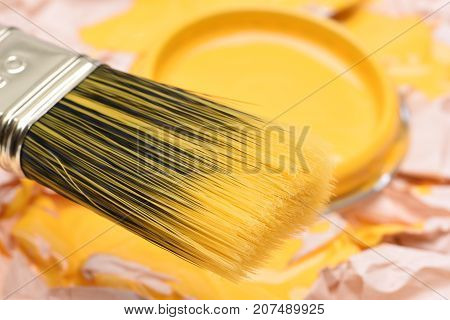 Paintbrush and can lid  with yellow paint, closeup