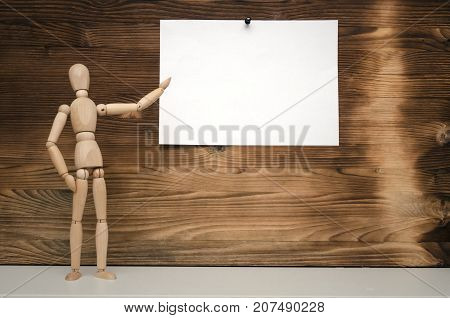 Product presentation. Special offer. Message board. To do list. Wooden doll newscaster. Wooden doll and blank empty white paper page on wooden wall background. Contact us or feedback form design.