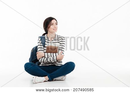 Portrait of a young smiling teenage girl with backpack holding books while sitting and looking away at copy space isolated over white background