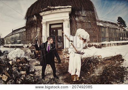 A Groom Swings An Ax Over The Bride In A White Fur Coat Against The Background Of The Building And W