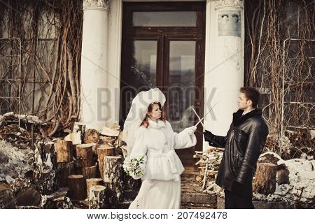 A Cheerful And Funny Bride And Groom In A White Fur Coat Fight With Icicles In A Winter Park Against