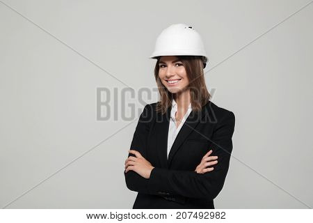 Portrait of a happy confident woman in hard hat and suit looking at camera with arms folded isolated over white background