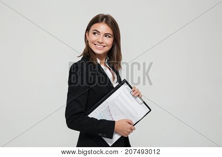 Portrait of a cheerful beautiful businesswoman in suit holding clipboard with documents and looking away isolated over white background