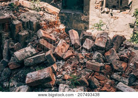 Red bricks of destroyed house by war, hurricane or other natural catastrophe or disaster, ruins of abandoned dwelling, toned
