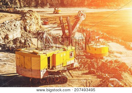 Quarry aggregate, heavy duty machinery. Construction industry. Sunset effect, toned
