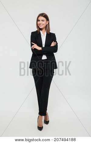 Full length portrait of an attractive smiling businesswoman in suit standing with arms folded and looking at camera isolated over white background