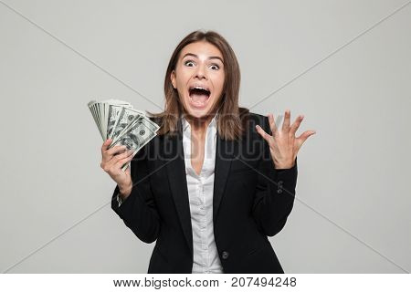 Portrait of an excited agitated businesswoman in suit holding bunch of money banknotes and looking at camera isolated over white background