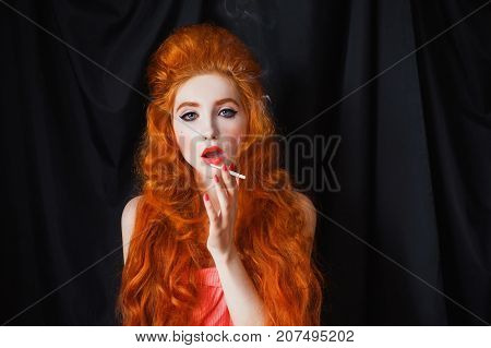 A smoking woman cigarette with pale skin and long curly red hair in a pink dress on a black background. Beautiful girl with cigarette and red lips with a cigarette in her hands Redhead model with cigarette. Sensual portrait with cigarette. To smoke a ciga