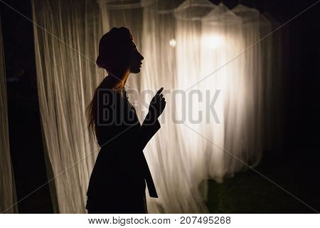Woman silhouette. Noir silhouette. Conceptual photo with silhouette. Silhouette in the night. Silhouette on a dark background. Silhouette in front of the lantern The white long canopies are illuminated by the light of the lantern on a dark night. Conceptu