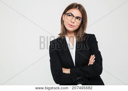 Portrait of smiling young businesswoman in suit standing with arms folded and looking away at copy space isolated over white background