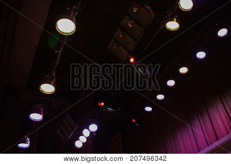 Color lighting in the concert stage. Color floodlights on the ceiling of stage. Soffits illuminate the stage. Electric light on stage. Equipment on stage for a concert. Big stage