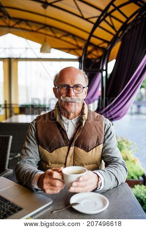 Elderly Man Having An Espresso On A Terrace Of Cafe