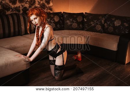 Fetish woman with pale skin and long red braids. Beautiful fetish slender girl with red lips in sexy fetish underwear. Beauty makeup. Redhead fetish model