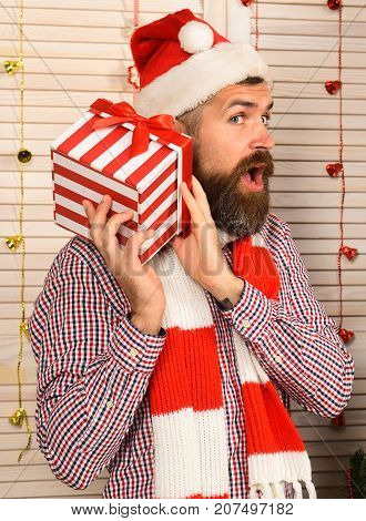 Guy Wears Santas Hat And Scarf. Man With Present Box