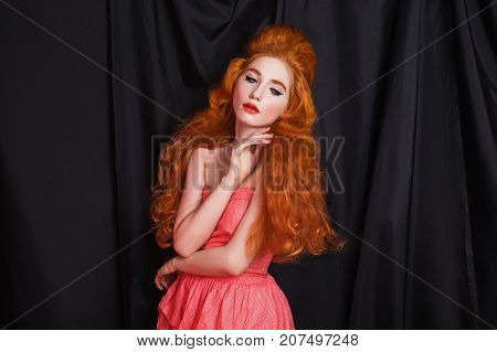 Curly woman with pale skin and long curly red hair in a pink dress on a black background. Beauty makeup. Redhead curly model. Sensual portrait of curly girl. Curly hair. Long curly hair