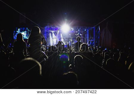 The crowd of spectators in front of the concert stage. Light from searchlights. A crowd of people. Crowd at the concert. Crowd in front of the light. The crowd is lit by a bright light. The crowd of spectators at the music festival