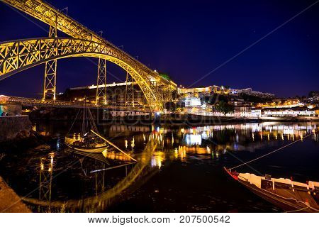 Iconic symbol of Oporto city. Scenic illuminated Dom Luis I bridge with boats reflecting on Douro River at night in Porto, Portugal's second largest city. Picturesque urban skyline.