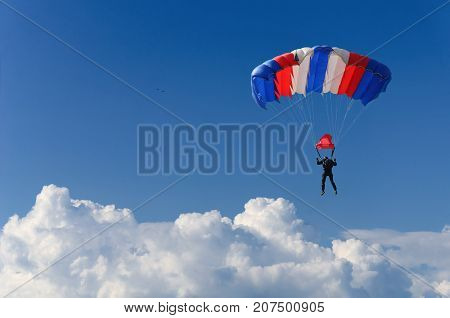 skydiver soars in the sky high above the clouds