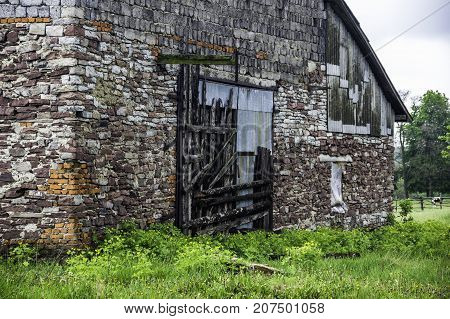 close-up of the gate of big abandoned brick barn in countryside