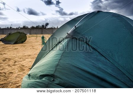 green camping tent on the beach at the stormy weather and broken tent at back