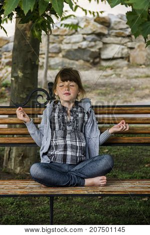 little caucasian girl meditates in a lotus pose on a bench