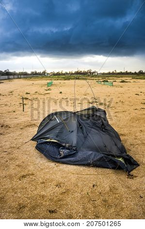 blue broken camping tent on the beach at the stormy weather