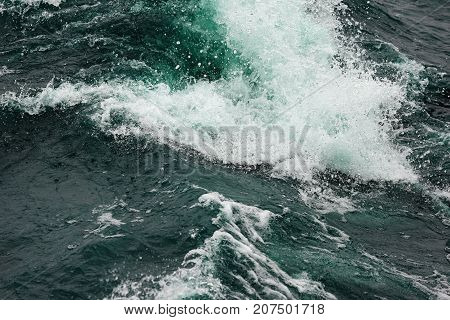 Boiling surface of water under the influence of strong wind. Splashes and drops of water scatter in different directions. Cold cyan water background.