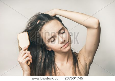 Happy woman combing hairs with comb, the girl with the closed eyes