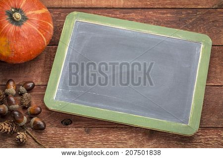 Blank slate blackboard against weathered barn wood with winter squash and acorn decoration, copy space