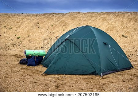 close-up green tourist tent at the sand