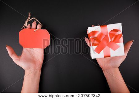 Close-up of female hands holding a red tag and a gift box on a black background.