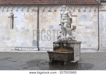 A Neptune sculpture in front of the Duomo in Carrara Tuscany Italy.