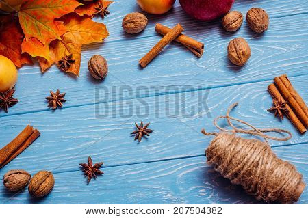 Blue wooden texture table on which lies balian, cinnamon sticks, walnuts, rope in a skein, walnuts and dry yellow maple leaves