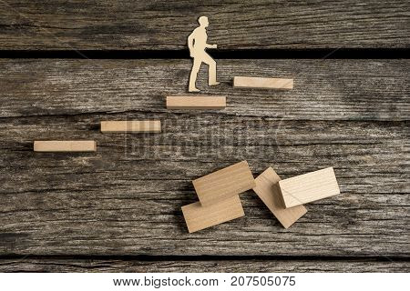 Silhouette cutouts of a man walking up wooden steps with dominos over old rough wooden table surface.