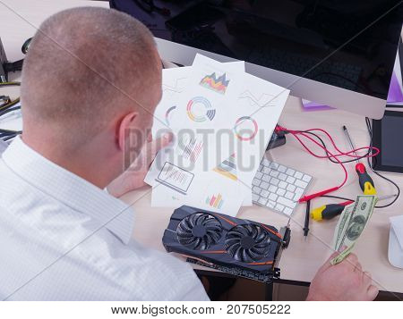 Close-up of a man from the back sits at the desk with a graphic card, money and graphs.